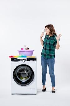 Vue de face jeune femme avec machine à laver et shampoings sur mur blanc