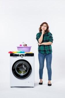 Vue de face d'une jeune femme avec une machine à laver et des shampooings pensant sur un mur blanc
