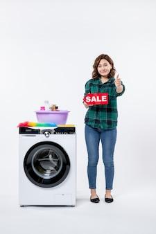 Vue de face d'une jeune femme avec une machine à laver tenant une bannière de vente sur un mur blanc