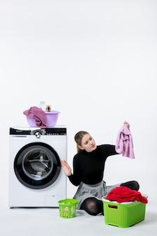 Vue de face jeune femme avec machine à laver et vêtements sales sur le mur blanc