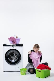 Vue de face jeune femme avec machine à laver et vêtements sales sur mur blanc