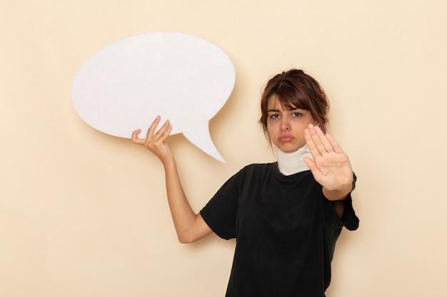 Vue de face jeune femme malade se sentir malade tenant un énorme panneau blanc sur une surface blanche légère