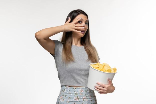 Vue de face jeune femme mangeant des chips de pomme de terre regarder un film sur la surface blanche légère