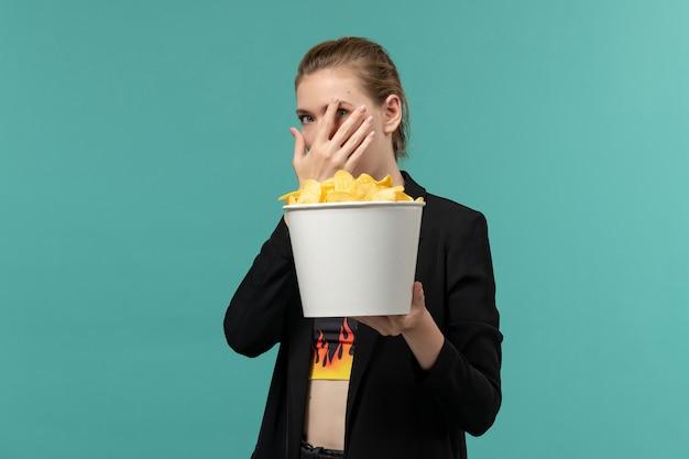 Vue de face jeune femme mangeant des chips de pomme de terre regarder un film sur la surface bleu clair