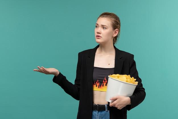 Vue de face jeune femme mangeant des chips de pomme de terre regarder un film sur la surface bleue