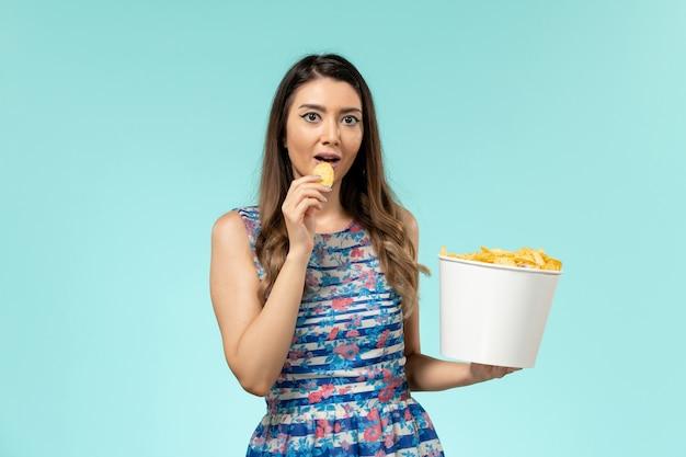 Vue de face jeune femme mangeant des cips sur une surface bleu clair
