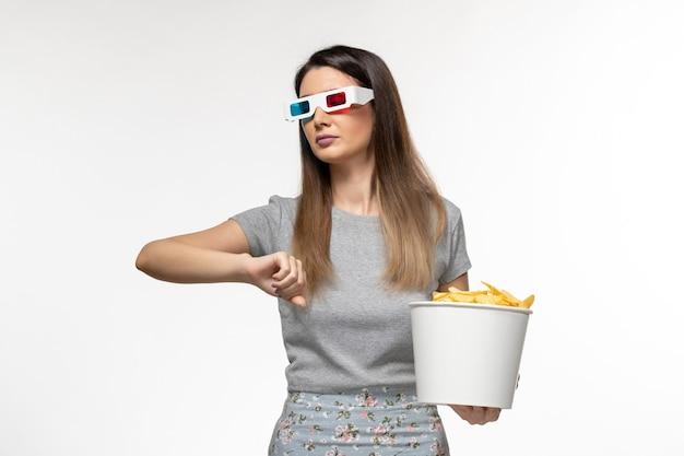 Vue de face jeune femme mangeant des cips tout en regardant un film dans des lunettes de soleil en regardant son poignet sur une surface blanche