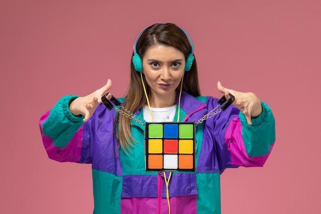 Vue de face jeune femme en manteau coloré tenant le sac sur le mur rose, femme modèle femme pose