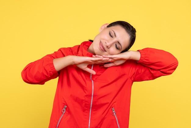 Vue de face jeune femme en manteau rouge dormant sur fond jaune