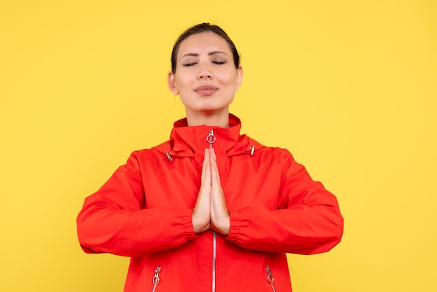Vue de face jeune femme en manteau rouge priant sur fond jaune