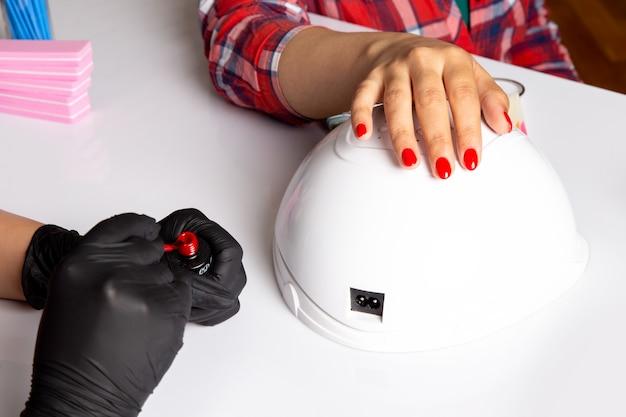 Une vue de face jeune femme manucure avec des gants noirs faisant manucure sur blanc