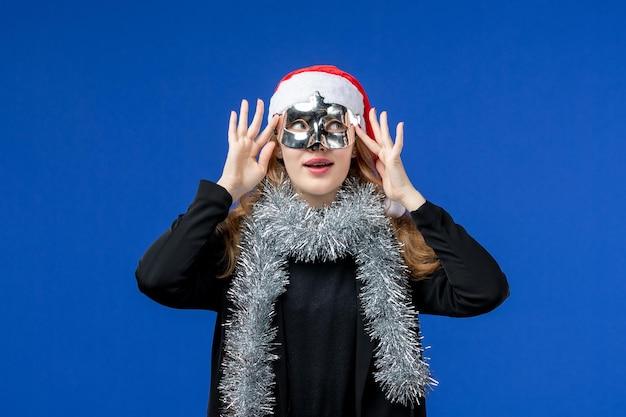Vue de face d'une jeune femme avec un masque d'argent sur un mur bleu