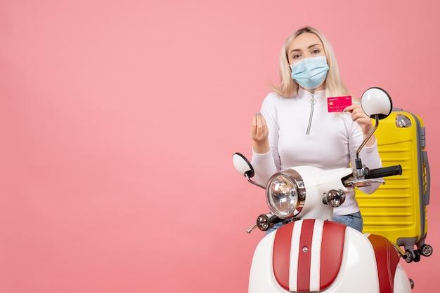 Vue de face jeune femme avec masque sur cyclomoteur avec valise jaune holding card
