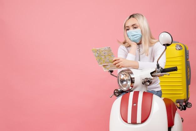 Vue de face jeune femme avec masque sur cyclomoteur avec valise jaune en regardant la carte