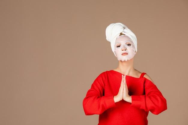 Vue de face jeune femme avec masque sur fond rose