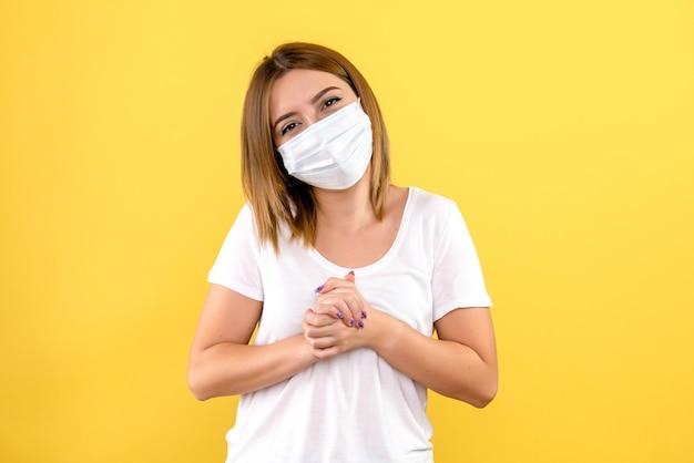 Vue de face de la jeune femme en masque sur un mur jaune