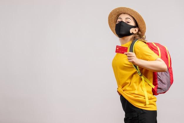 Vue de face jeune femme avec masque noir brandissant la carte