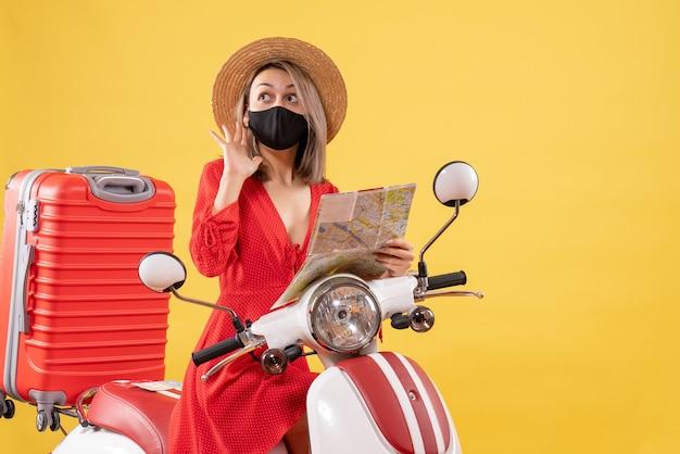Vue de face jeune femme avec masque noir sur cyclomoteur holding map