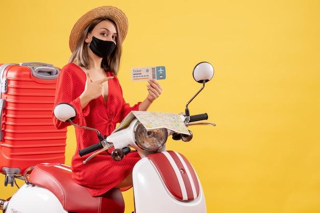 Vue de face jeune femme avec masque noir sur cyclomoteur pointant sur billet d'avion