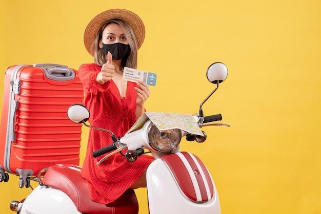 Vue de face jeune femme avec masque noir sur un cyclomoteur tenant un billet donnant le pouce