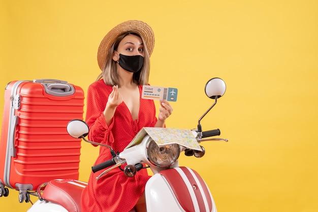 Vue de face jeune femme avec masque noir sur cyclomoteur tenant un billet faisant de l'argent signe