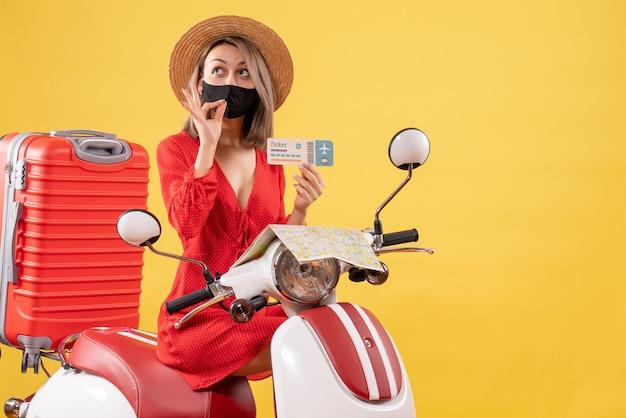 Vue de face jeune femme avec masque noir sur un cyclomoteur tenant un billet faisant un signe savoureux