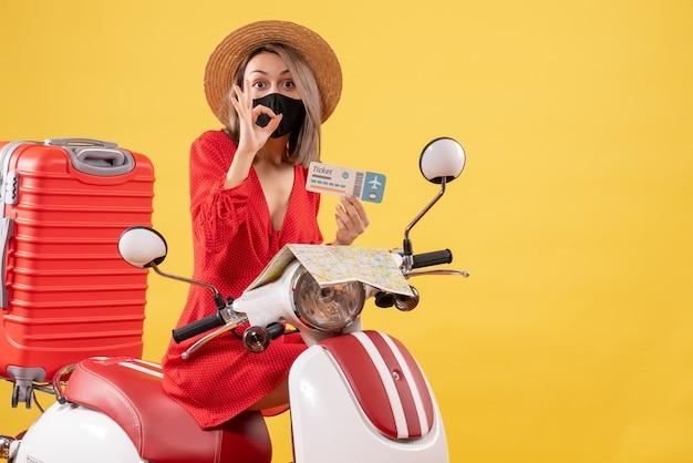 Vue de face jeune femme avec masque noir sur cyclomoteur tenant un billet gesticulant signe okey