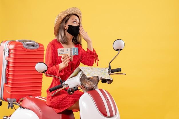 Vue de face jeune femme avec masque noir sur cyclomoteur avec valise rouge tenant un billet bâillant