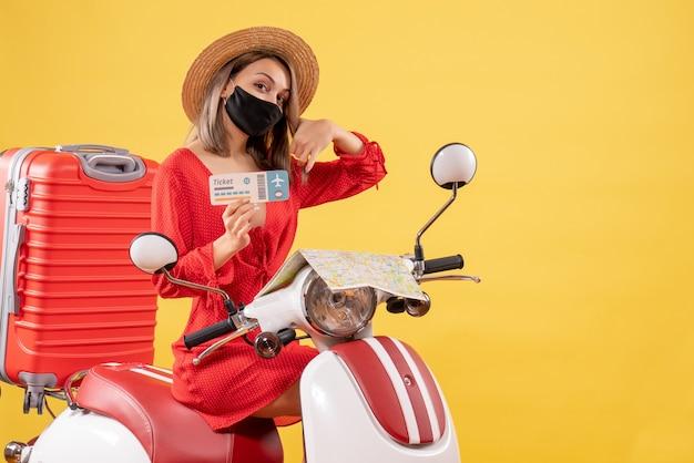 Vue de face jeune femme avec masque noir sur cyclomoteur avec valise rouge tenant un billet faisant appel moi signe