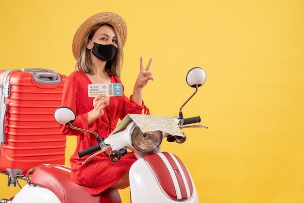 Vue de face jeune femme avec masque noir sur cyclomoteur avec valise rouge tenant un billet gesticulant le signe de la victoire