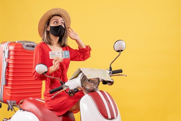 Vue de face jeune femme avec masque noir sur cyclomoteur avec valise rouge tenant un billet regardant quelque chose