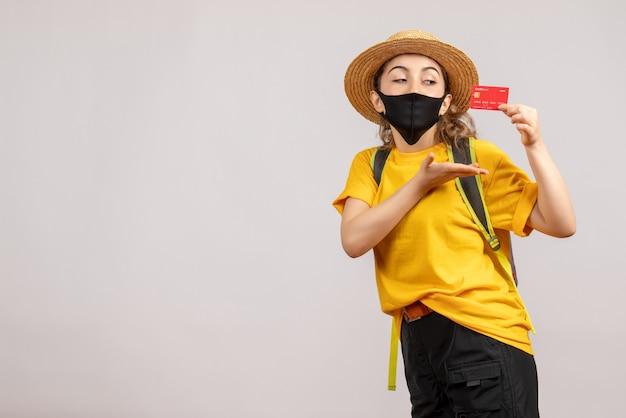 Vue de face jeune femme avec masque noir holding card