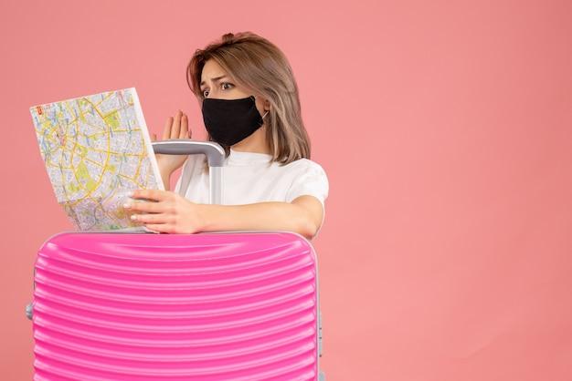 Vue de face jeune femme avec masque noir en regardant la carte