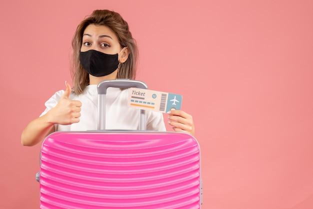 Vue de face jeune femme avec masque noir tenant un billet donnant les pouces vers le haut
