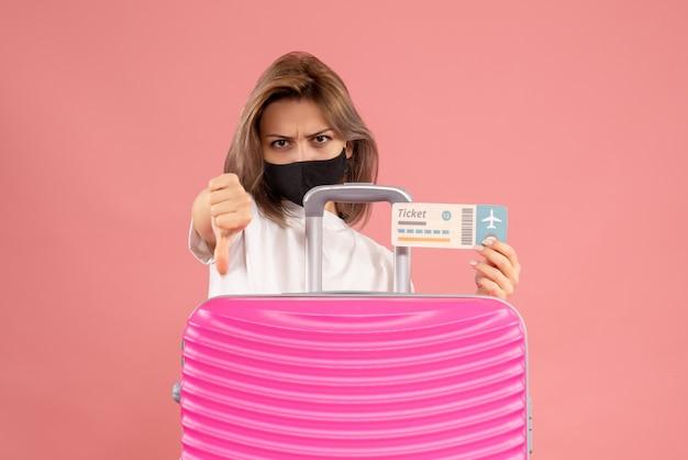 Vue de face jeune femme avec masque noir tenant un billet faisant signe de pouce vers le bas debout derrière une valise rose