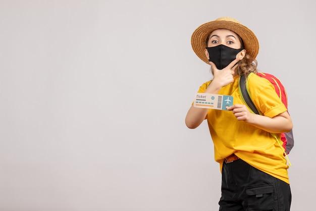 Vue de face jeune femme avec masque noir tenant un billet de voyage mettant la main sur son menton