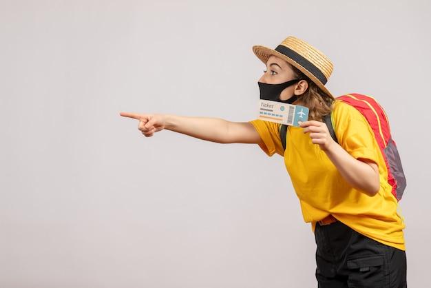 Vue de face jeune femme avec masque noir tenant un billet de voyage pointant vers la gauche