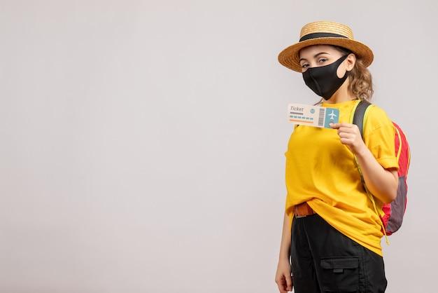 Vue de face jeune femme avec masque noir tenant un billet de voyage
