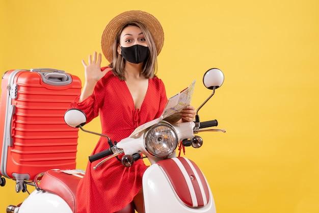 Vue de face jeune femme avec masque noir tenant une carte en agitant la main près d'un cyclomoteur