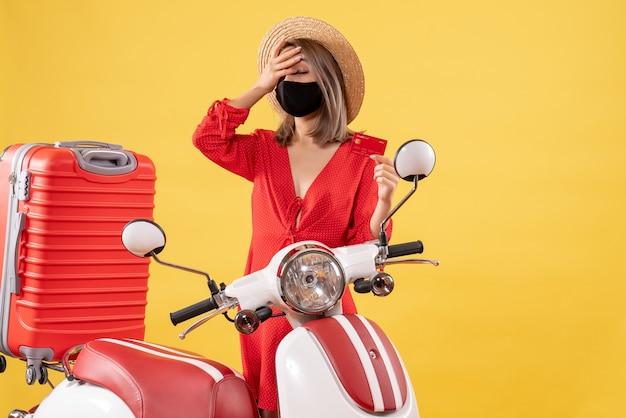 Vue de face jeune femme avec masque noir tenant une carte de crédit debout près de la valise rouge du cyclomoteur