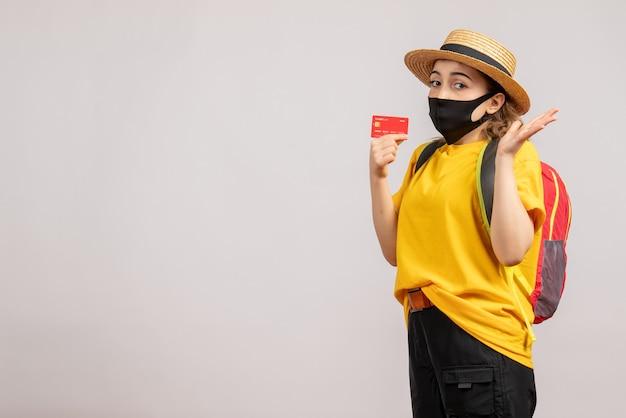 Vue de face jeune femme avec masque noir tenant une carte de crédit