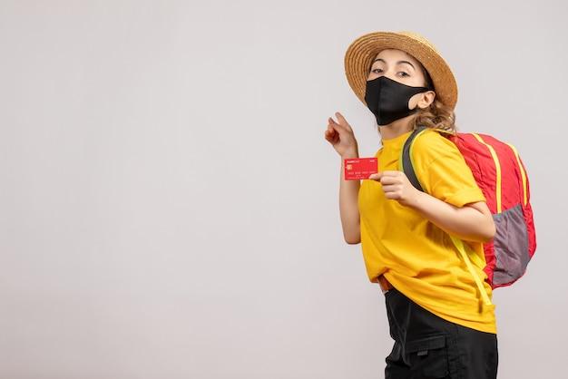 Vue de face jeune femme avec masque noir tenant la carte doigt pointé derrière