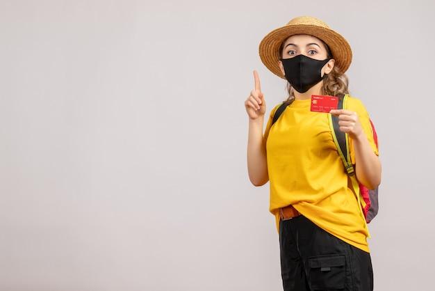 Vue de face jeune femme avec masque noir tenant la carte doigt pointé vers le haut