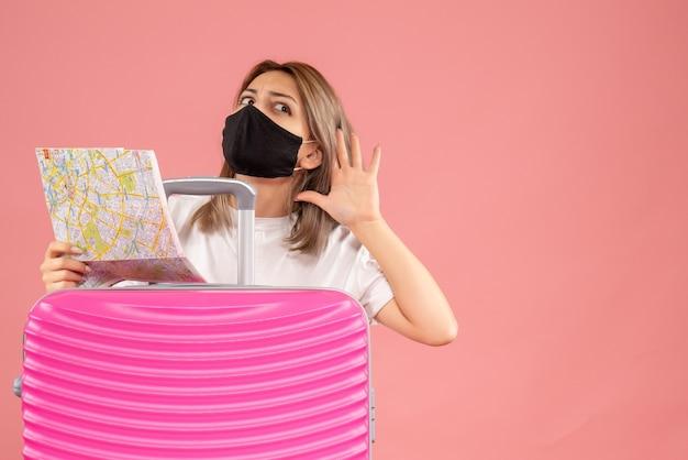 Vue de face jeune femme avec masque noir tenant une carte écoutant quelque chose derrière une valise rose
