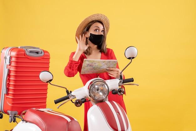 Vue de face jeune femme avec masque noir tenant une carte écoutant quelque chose près d'un cyclomoteur