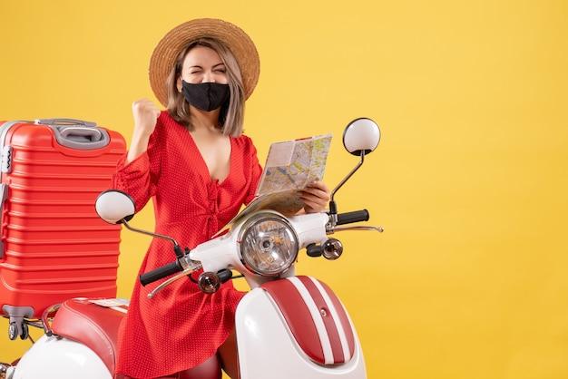 Vue de face jeune femme avec masque noir tenant une carte exprimant son bonheur près d'un cyclomoteur