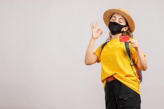Vue de face jeune femme avec masque noir tenant une carte gesticulant signe ok