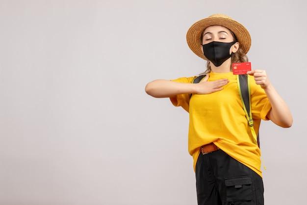 Vue de face jeune femme avec masque noir tenant une carte mettant la main sur sa poitrine