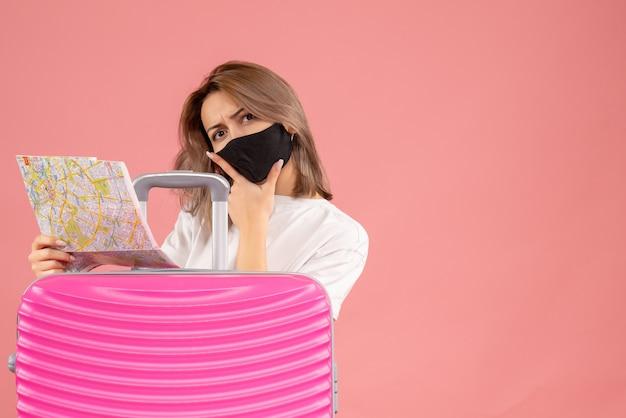 Vue de face jeune femme avec masque noir tenant une carte mettant la main sur son menton