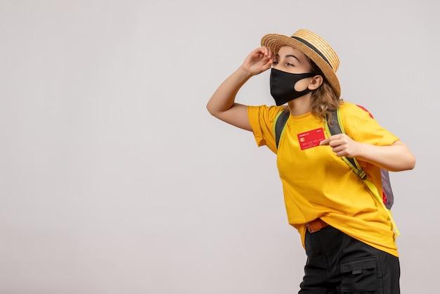 Vue de face jeune femme avec masque noir tenant une carte d'observation